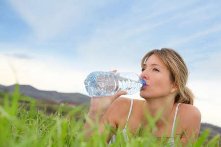 Beautiful blond woman drinking water in natural landscape photo