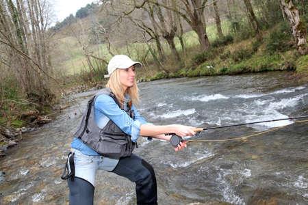 flyfishing: Woman fly-fishing in river