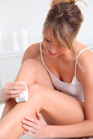 Beautiful woman shaving her legs photo