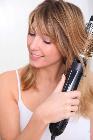 curling: Beautiful blond woman curling her hair
