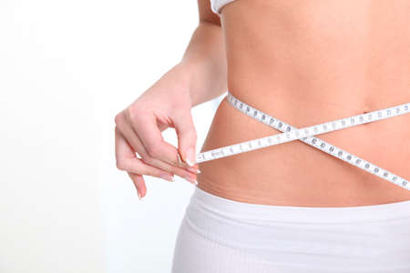 Slim womans waist and measure tape photo