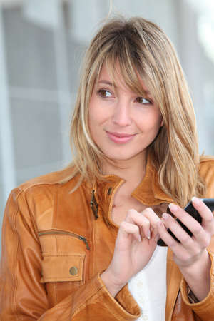 Woman in town sending short message with mobile phone photo