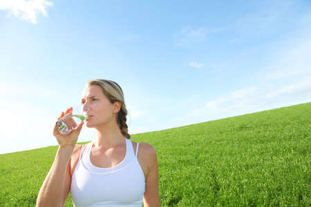hydrate: Woman drinking natural water in green field Stock Photo