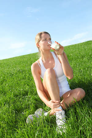 Beautiful blond woman drinking milk in countryside photo