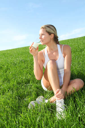 woman drinking milk: Beautiful blond woman drinking milk in countryside