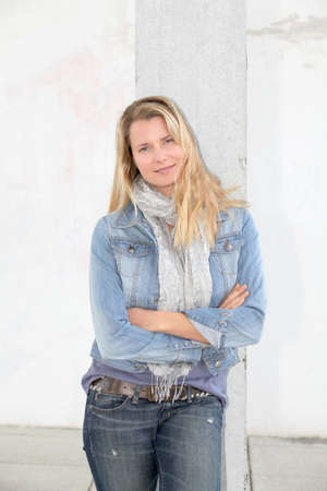 Blond woman standing on concrete wall photo