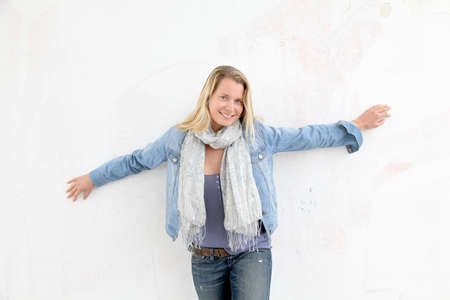 Blond smiling woman leaning against wall photo