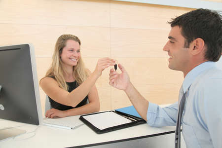 Woman giving car key to businesssman photo