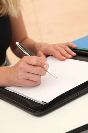 Closeup of woman signing contract photo