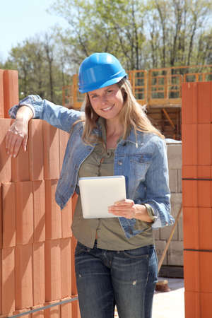 Smiling architect on building site with electronic tablet photo