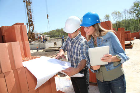 Engineers on construction site with plan photo
