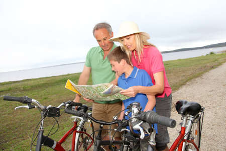 Family on bicycle ride looking at map Stock Photo - 9479215