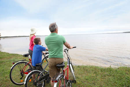 activity holiday: Family on a bike ride standing by a lake Stock Photo
