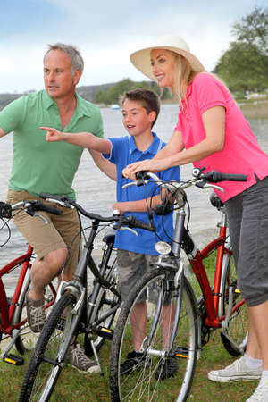 Family on a bike ride standing by a lake photo