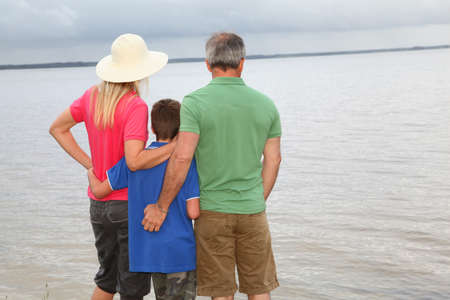 Family of three people on lake side photo