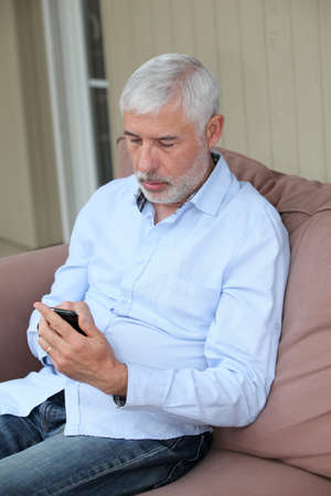 Senior man sending message with mobile phone photo