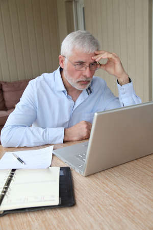 Senior businessman working at home photo