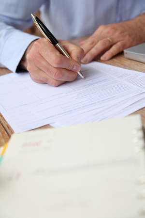 autograph: Closeup of senior man filling in tax form