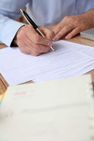 firmando: Detalle de hombre senior rellenando el formulario de impuestos Foto de archivo