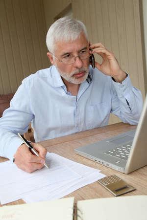 Senior man talking on mobile phone photo