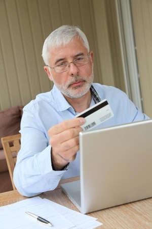Senior man doing online shopping photo