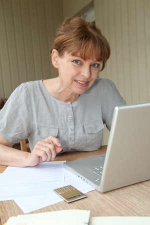 filling out: Senior woman filling out form with help of internet