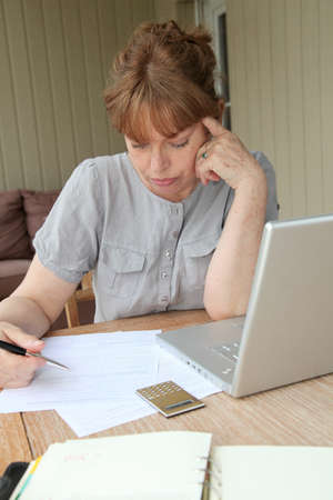 Senior woman filling out form with help of internet