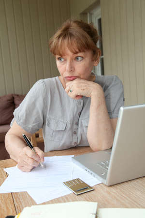 Senior woman filling out form with help of internet photo