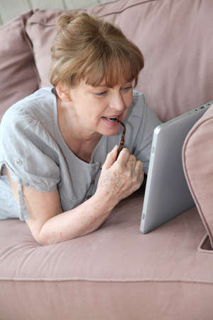Senior woman using electronic tablet at home photo