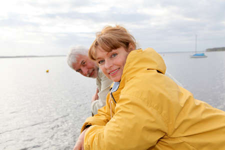 raincoat: Portrait of senior couple standing by a lake