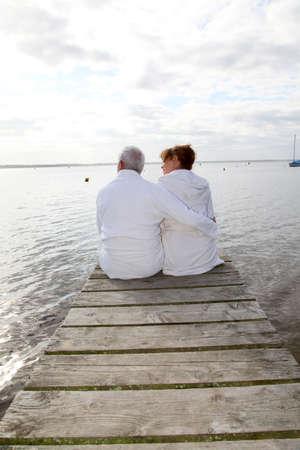 bathrobes: Par Senior en albornoz sentado en un pont�n Foto de archivo