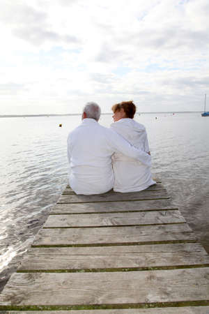 Senior couple in bathrobe sitting on a pontoon photo
