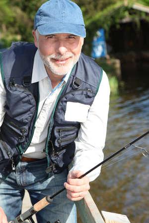 Portrait of smiling senior fisherman photo
