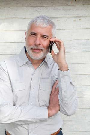 Portrait of senior man talking on the phone photo