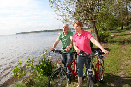 Senior couple on bicycle ride by a lakeside photo