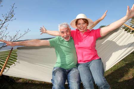 balancing: Happy senior couple sitting in hammock