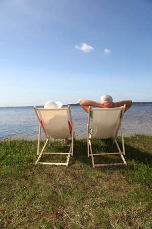 backview: Senior couple in deck chairs in front of a lake