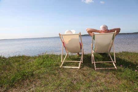 tercera edad: Par Senior en sillas de un lago