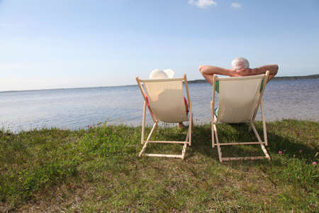 lake front: Senior couple in deck chairs in front of a lake