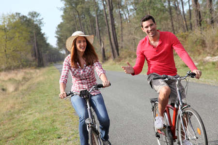 Couple riding bicycles in countryside photo