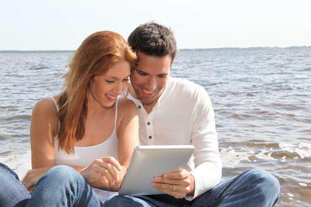 android tablet: Couple using electronic tablet by a lake