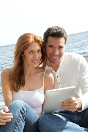 Couple using electronic tablet by a lake photo
