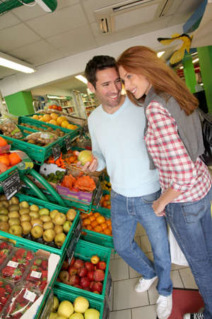 Couple at the supermarket doing grocery shopping Stock Photo - 9784529