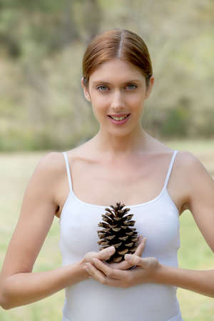 Portrait of beautiful woman holding pine cone