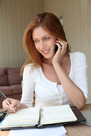 home phone: Self-employed woman at home talking on the phone Stock Photo