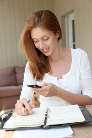 selfemployed: Self-employed woman at home talking on the phone Stock Photo