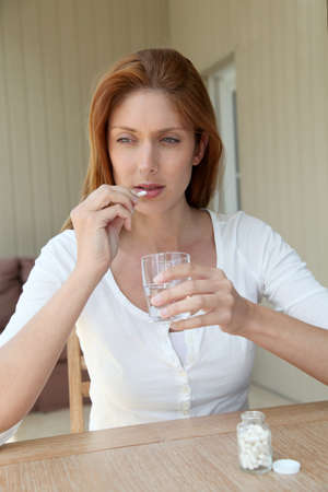 at ease: Woman taking pills to ease headache Stock Photo