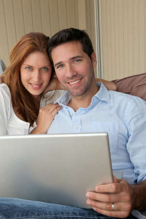 Couple sitting in couch with laptop computer photo