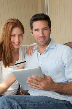 Couple doing online shopping with electronic tablet photo