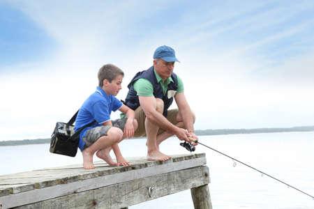 hombre pescando: Padre e hijo de pesca en el lago